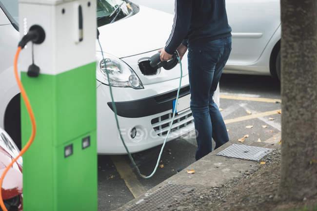 Section basse de l'homme, voiture électrique à la station de recharge de charge — Photo de stock