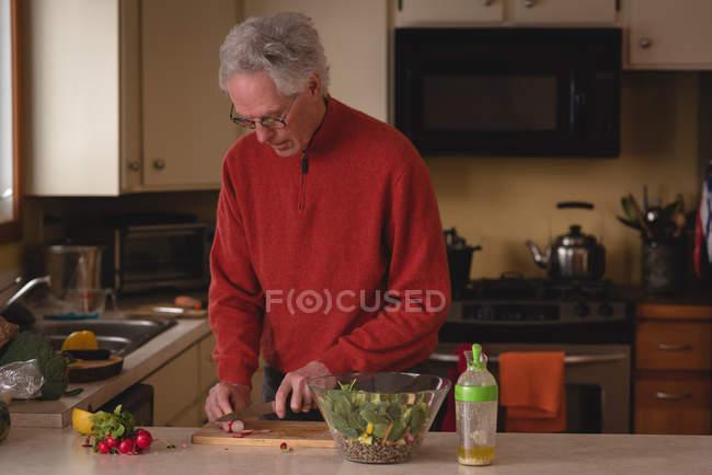 Uomo anziano affettare verdura con coltello sul tagliere in cucina — Foto stock