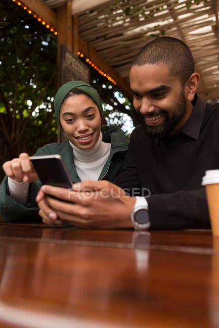 Счастливая пара, используя мобильный телефон в кафе — стоковое фото