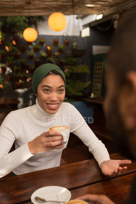 Happy couple interacting with each other while having coffee in cafe — Stock Photo