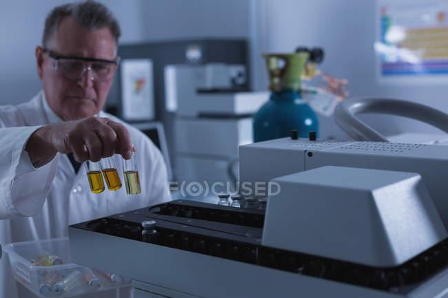 Científico masculino colocando botella química en una máquina en laboratorio - foto de stock