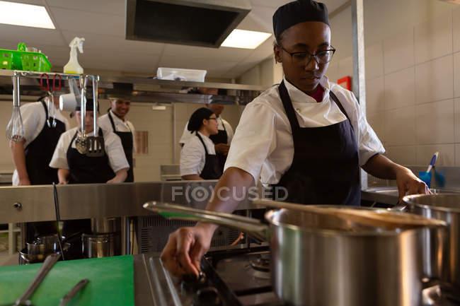 Female chef working in kitchen at restaurant — Stock Photo
