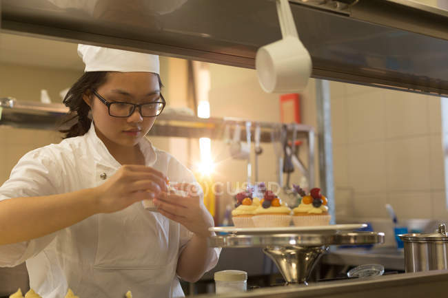 Chef mujer guarnición muffins en cocina de restaurante - foto de stock