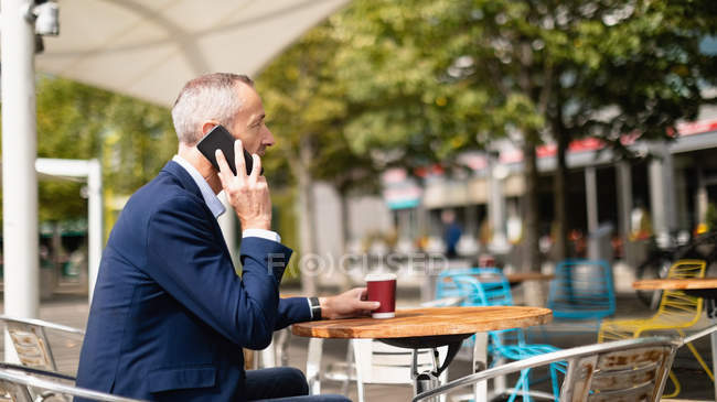 Seitenansicht eines Geschäftsmannes, der im Outdoor-Café mit dem Handy telefoniert — Stockfoto