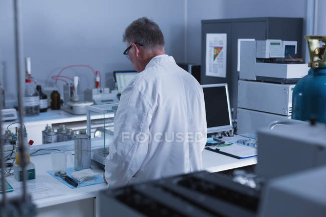 Rear view of male scientist experimenting in laboratory — Stock Photo