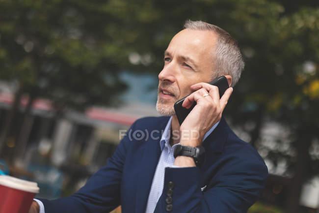 Nahaufnahme eines Geschäftsmannes, der im Outdoor-Café mit dem Handy telefoniert — Stockfoto