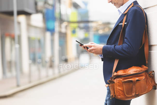 Mid section businessman using mobile phone in city — Stock Photo