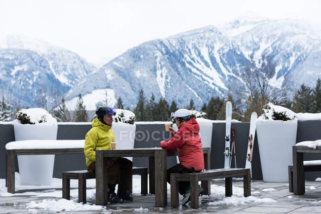 Coppia anziana che interagisce mentre prende un caffè in inverno — Foto stock