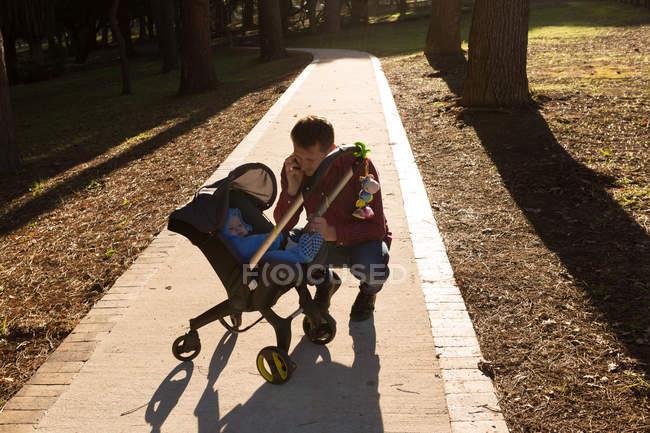 Padre con il suo bambino in carrozzina nel parco in una giornata di sole — Foto stock