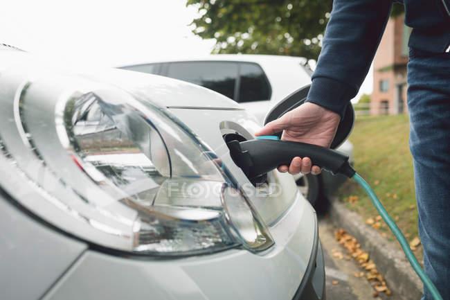 Gros plan de l'homme, voiture électrique à la station de recharge de charge — Photo de stock