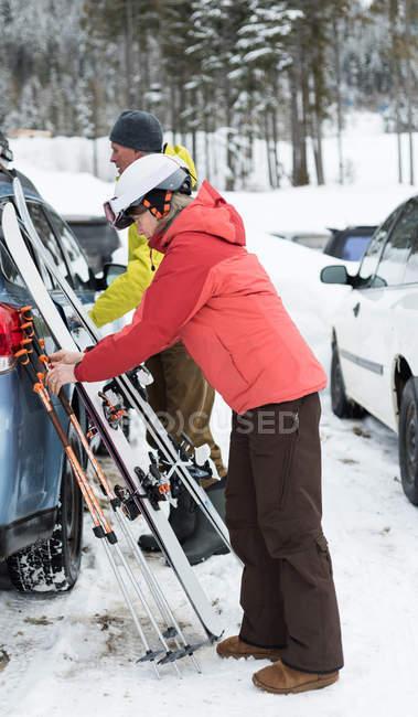 Пожилые супружеские пары, в ведение Совета лыж и лыжные палки возле автомобиля в зимнее время — стоковое фото