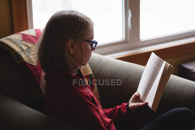 Senior woman reading book on arm chair in living room at home — Stock Photo