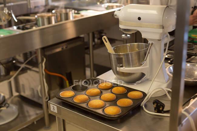 Muffins dans un plateau et pétrisseuse dans la cuisine — Photo de stock