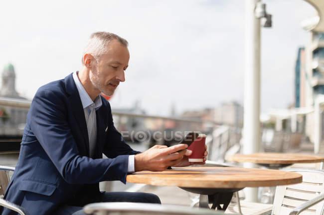 Seitenansicht eines Geschäftsmannes, der sein Handy im Outdoor-Café benutzt — Stockfoto