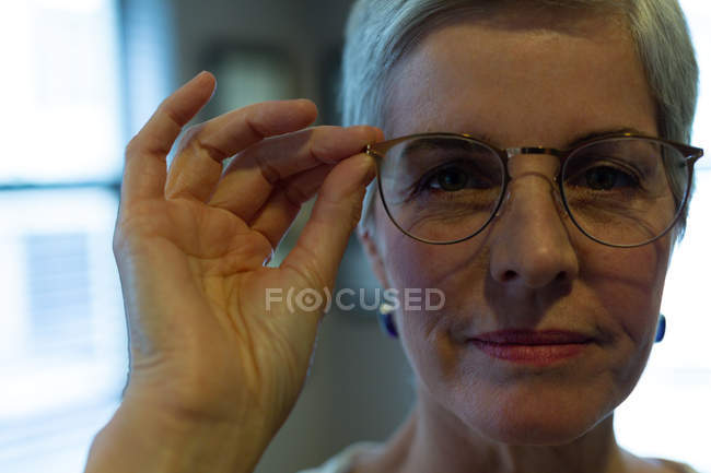 Close-up senior woman looking at camera while holding eyeglasses in clinic — Stock Photo