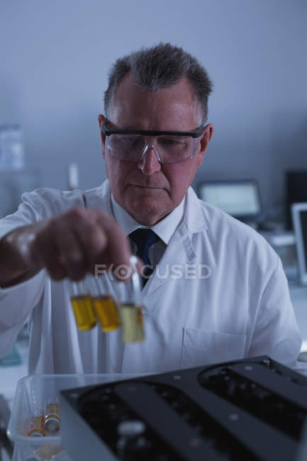Male scientist placing chemical bottle on a machine in laboratory 4k — Stock Photo