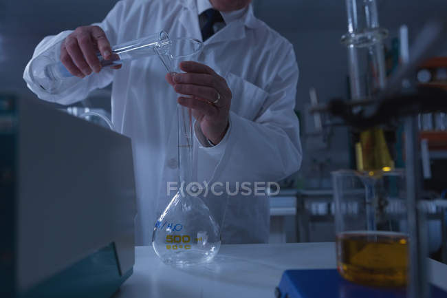 Mid section of male scientist experimenting in laboratory — Stock Photo