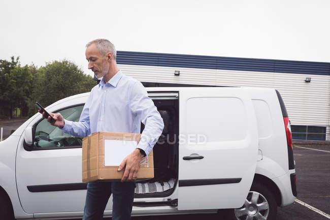 Доставщик с мобильного телефона на складе — стоковое фото