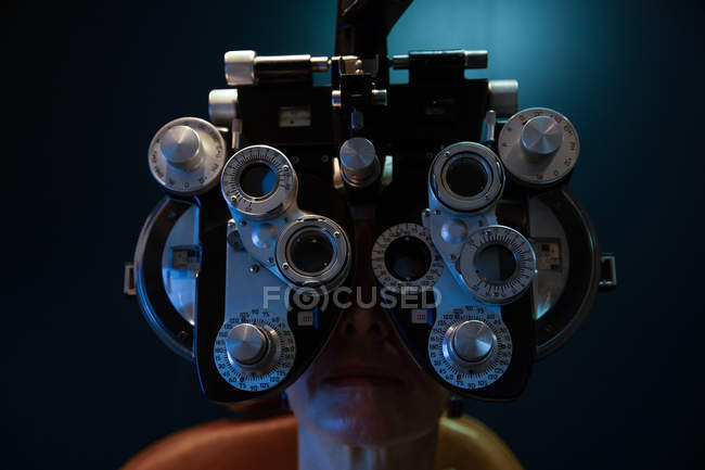 Close-up of optometrist examining patient eyes with phoropter in clinic — Stock Photo