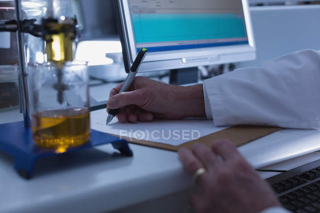 Close-up of male scientist writing on clipboard in laboratory — Stock Photo