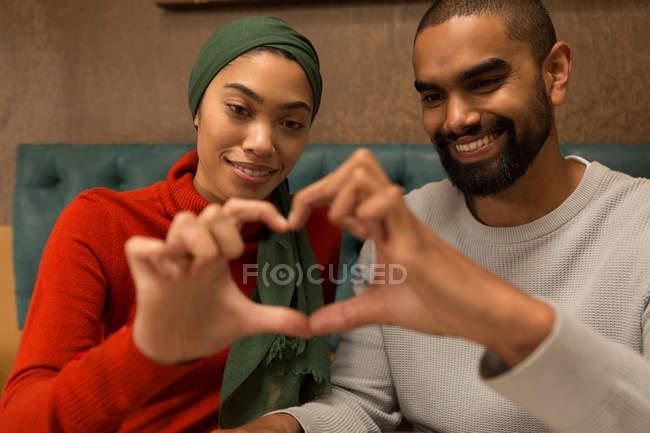Casal feliz, fazendo o símbolo do coração com as mãos — Fotografia de Stock