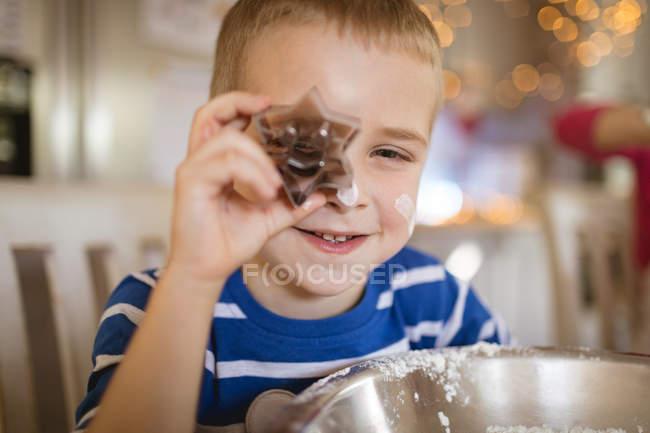 Крупный план улыбающегося мальчика, показывающего нож для печенья — стоковое фото