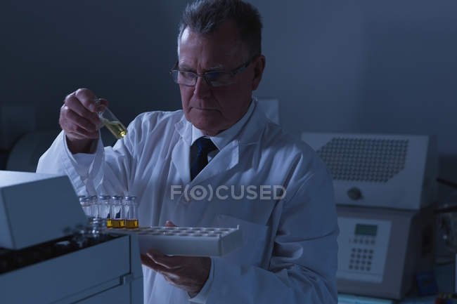 Homme scientifique plaçant des flacons médicaux sur une machine de laboratoire en laboratoire — Photo de stock
