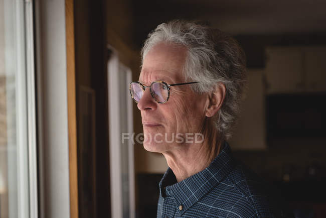 Thoughtful senior man looking through window at home — Stock Photo