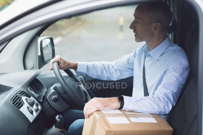 Вид сбоку грузчика с пакетом за рулем грузового фургона — стоковое фото