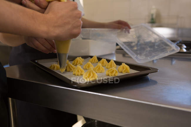Mid section of chef using pastry bag in kitchen at restaurant — Stock Photo