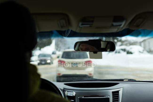 Rear view of senior man driving a car on street — Stock Photo
