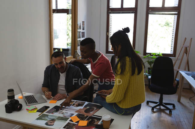 Business colleagues discussing over a photos on desk at office — Stock Photo