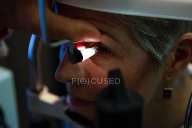 Primer plano del optometrista examinando los ojos del paciente con equipo de prueba ocular en la clínica - foto de stock