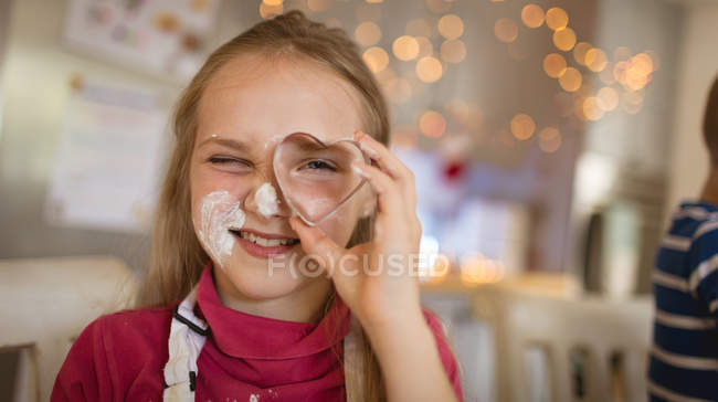 Menina sorridente mostrando um cortador de biscoitos em forma de coração — Fotografia de Stock