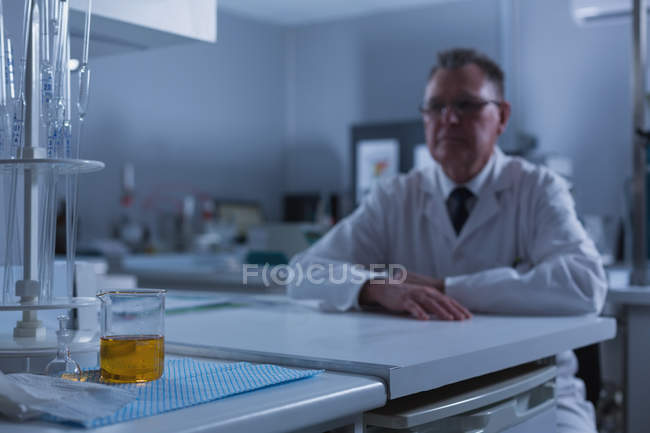Male scientist sitting at table in laboratory — Stock Photo