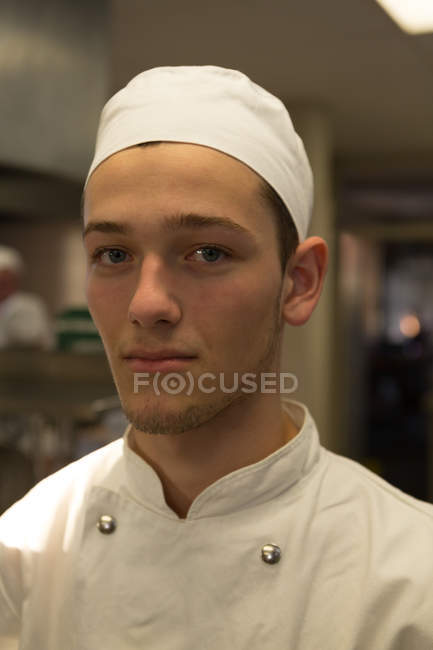Portrait of male chef standing in kitchen at restaurant — Stock Photo