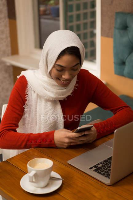 Счастливая женщина, используя мобильный телефон в кафе — стоковое фото