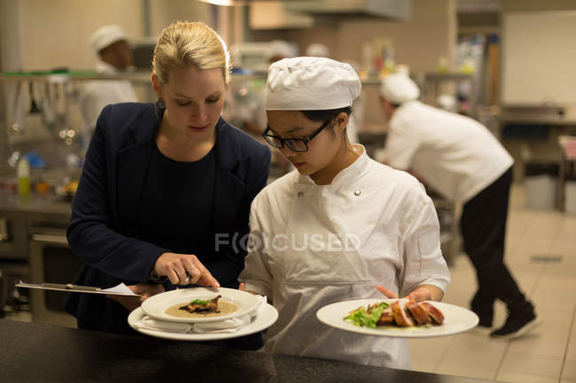 Female manager and female chefs interacting with each other in kitchen — Stock Photo