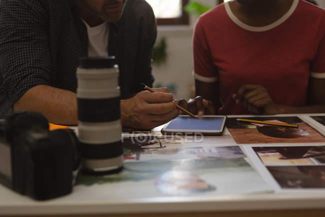 Section médiane de collègues de travail, discuter sur une tablette numérique au bureau — Photo de stock