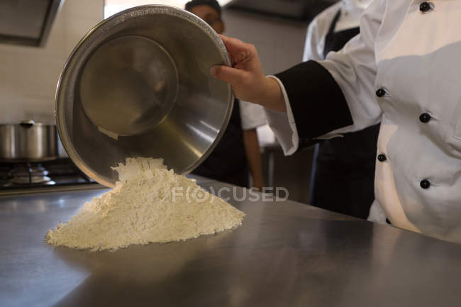 Mid section of female chef pouring flour on worktop in kitchen — Stock Photo