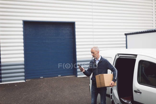 Доставки людини за допомогою мобільного телефону на складі — стокове фото