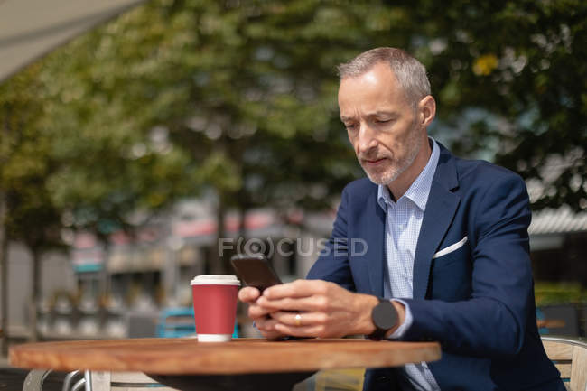 Businessman using mobile phone at outdoor cafe on a sunny day — Stock Photo