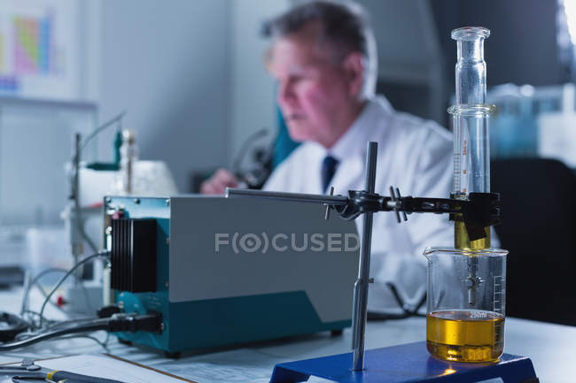Close-up of glass syringe with stand and beaker arranged on table in laboratory — Stock Photo