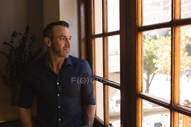 Thoughtful male executive looking through window in office — Stock Photo