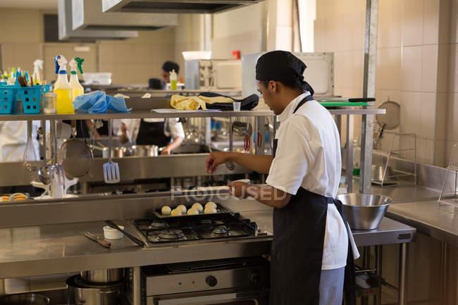 Чоловічий шеф-кухар поширення борошна на тісто кулі в кухні — стокове фото