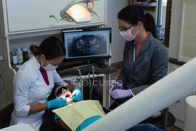 Dentiste et infirmière examinant la patiente avec des outils en clinique — Photo de stock