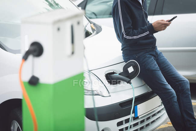 Mid section of man using mobile phone while charging electric car at charging station — Stock Photo