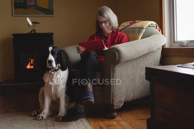 Mujer usando tableta digital con perro sentado a su lado en la sala de estar - foto de stock