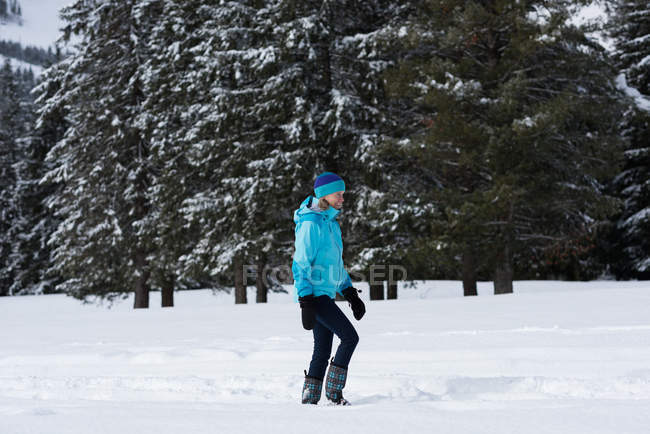 Side view of senior woman in winter clothing standing at snowy landscape — Stock Photo