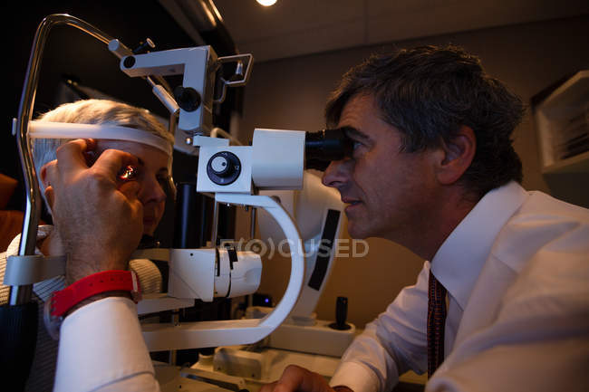 Оптометрист осматривает глаза пациентов с щелевой лампой в клинике — стоковое фото